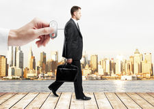 Control concept. Hand turning winder on business person's back. City view background. Control concept Stock Photography