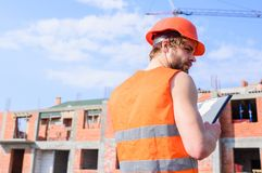 Control construction process. Builder orange vest and helmet works at construction site. Contractor control according to royalty free stock image