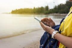Control de la mano de la mujer joven y teléfono elegante de la pantalla táctil en la playa y Foto de archivo