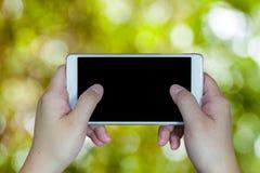 Control de la mano de la mujer y teléfono elegante del tacto Fotos de archivo