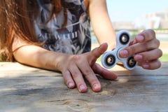 Control de la mano de las mujeres un hilandero blanco Foto de archivo