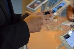 Control de la mano del hombre de negocios un teléfono Fotos de archivo