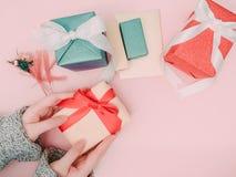 Control de la mano del ` s de la muchacha de la belleza la caja de regalo del oro con el arco rojo f de la cinta Fotografía de archivo libre de regalías