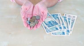 Control de la mano de la empresaria que un yen japonés de la moneda acuñan y la prohibición de los yenes Foto de archivo libre de regalías
