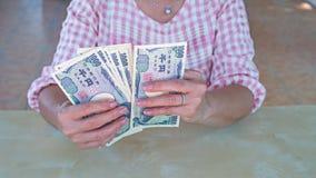 Control de la mano de la empresaria un billete de banco japonés de los yenes de la moneda Fotos de archivo libres de regalías