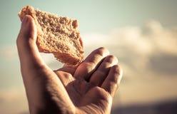 Control de la mano una rebanada de pan. Imagen de archivo