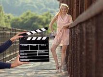 Control de la muestra de Clapperboard por las manos femeninas Imagenes de archivo