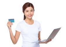 Control de la mujer joven con el ordenador portátil y la tarjeta de crédito Imagen de archivo libre de regalías