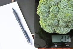 Control de peso - escala de cristal negra de la cocina con bróculi, el lápiz y el papel verdes Imagen de archivo