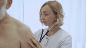 Control del cardiólogo los pulmones del hombre mayor con el estetoscopio almacen de metraje de vídeo