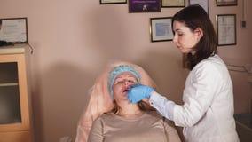 Control del Cosmetologist la condición del paciente después de la inyección de Botox almacen de metraje de vídeo