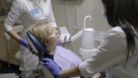 Control del dentista muy cuidadosamente ascendente y diente de la reparación de su paciente femenino almacen de metraje de vídeo