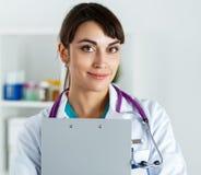 Control del doctor y cojín femeninos sonrientes hermosos del tablero del abrazo Fotos de archivo libres de regalías