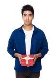 Control del hombre joven con el giftbox rojo Imágenes de archivo libres de regalías