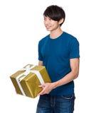 Control del hombre joven con la caja de regalo Imágenes de archivo libres de regalías