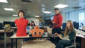 Control del hombre y de la mujer un robot, usando los ordenadores portátiles, cierre para arriba metrajes