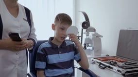 Control del niño pequeño su vista en oficina del oculista almacen de video