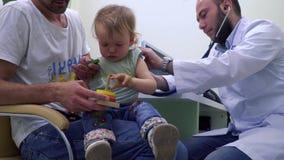 Control del pediatra el heartbeating de la niña con el estetoscopio almacen de video