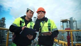 Control del trabajador de dos fábricas y discusión trabajando tecnología con el documento de papel y la PC de la tableta almacen de metraje de vídeo
