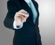 Control derecho de la mano de la postura del hombre de negocios una pluma aislada foto de archivo libre de regalías