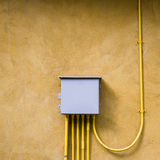 Control electrical box on yellow wall. Royalty Free Stock Image