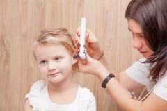 Control ENT del niño - oído de examen del doctor de una niña con oto fotografía de archivo