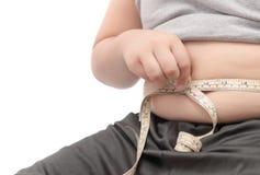Control gordo del niño hacia fuera sus grasas de cuerpo con la cinta métrica Imagen de archivo libre de regalías