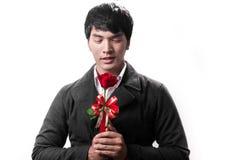 Control hermoso asiático del hombre la rosa roja con amor Imagen de archivo libre de regalías