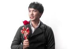 Control hermoso asiático del hombre la rosa roja con amor Imagenes de archivo