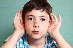 Control hermoso del muchacho del preadolescente que el suyo oye aislado en azul fotos de archivo libres de regalías