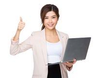 Control joven asiático de la empresaria con el ordenador portátil y el pulgar foto de archivo libre de regalías