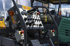 Control panel of asphalt paving machine. Heavy industry, dashboard unit with buttons, levers, toggle switches, knobs, signal lights, sensors, indicators and Royalty Free Stock Images