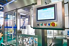 Control panel monitor on conveyor at food factory for packing. Conveyor at food factory for packing plastic containers stock image