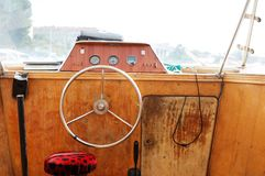 Control panel with steering wheel of the old motor boat Stock Photos