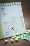 Control pills on a calendar. Control pills on a  may calendar, concept of pharmaceutical copayment Stock Photography