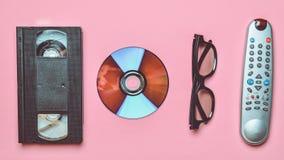 Control remoto, 3d vidrios, CD, cinta de video en un fondo en colores pastel rosado Tecnología retra fotografía de archivo libre de regalías