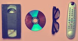 Control remoto, 3d vidrios, CD, cinta de video en un rosa imagen de archivo libre de regalías