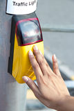 Control traffic light. Hand presses the button on the pedestrian crossing Stock Photos
