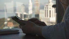 Control y charla de la muchacha sobre un teléfono por la ventana almacen de video