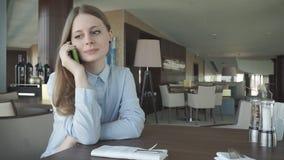 Control y charla de la muchacha sobre un teléfono por la ventana metrajes