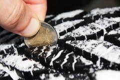Controlando profundidad de pisada del neumático con un euro dos acuñe Fotos de archivo libres de regalías