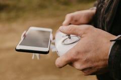 Controlando um zangão remoto do helicóptero com estreia do smartphone fotos de stock royalty free