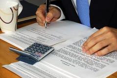 Controlando y firmando el contrato y/o el arriendo Imagen de archivo libre de regalías