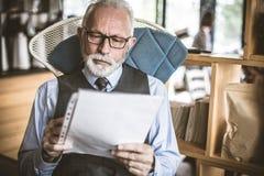 Controlar documentos Hombre de negocios mayor imagen de archivo