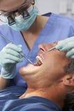 Controlar femenino de Giving Male Patient del dentista Imagen de archivo