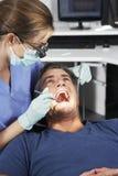 Controlar femenino de Giving Male Patient del dentista Fotografía de archivo