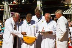Controlar la calidad del queso en el mercado de Alkmaar Foto de archivo libre de regalías