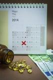 Controle comprimidos em um calendário Imagem de Stock