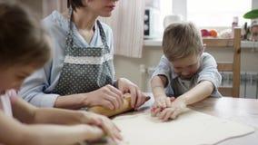 Controle da mamã como as crianças fazem biscoitos com sua câmera do fluxo de moldes filme