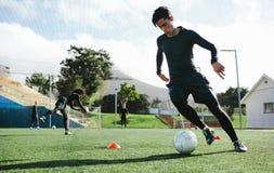 Controle de bola praticando do jogador de futebol foto de stock